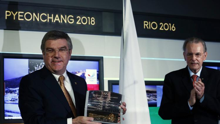 IOC President Bach poses with the presidency key next to his predecessor Rogge during a ceremony in Lausanne