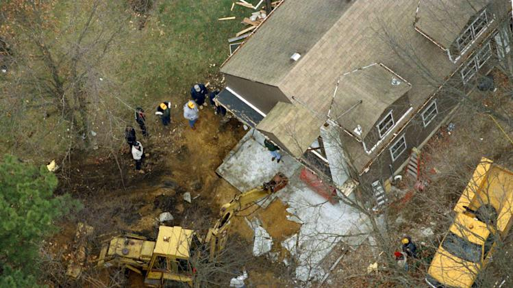 "FILE - In this Jan. 17, 1993 file photo, officials employ a backhoe to break up a slab of concrete that covers a subterranean room behind a carport at the home of John Esposito in Bay Shore, N.Y., where he held Katie Beers for 17 days. On the 20th anniversary of her ordeal, Beers has co-written a book with a television reporter who covered her kidnapping. ""Buried Memories: Katie Beers' Story"" (Title Town Publishing) has a happy ending.  (AP Photo/Alex Brandon, File)"
