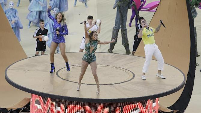 Brazilian singer Claudia Leitte, left, US singer Jennifer Lopez and rapper Pitbull perform during the opening ceremony ahead of the group A World Cup soccer match between Brazil and Croatia, the opening game of the tournament, in the Itaquerao Stadium in Sao Paulo, Brazil, Thursday, June 12, 2014. (AP Photo/Thanassis Stavrakis)