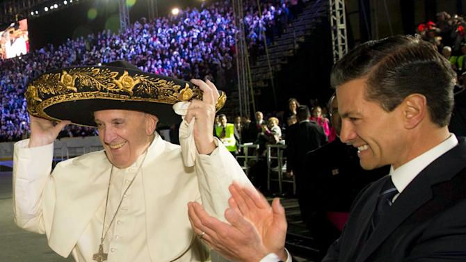Pope Francis tries on a Mariachi hat as Mexico's President Enrique Pena Nieto applauds after his arrival in Mexico City