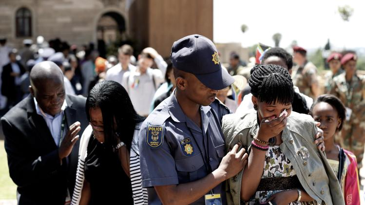 Women are consoled after paying their respects to former South African President Mandela in Pretoria