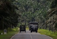 Malaysian police and military trucks are shown in Lahad Datu on Borneo island, on March 3, 2013. Malaysia vowed to beef up security in an area where at least 26 people have been reported killed after a bizarre invasion by Philippine followers of a self-styled sultan.