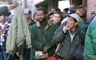 Homeless people stand in line for coats.