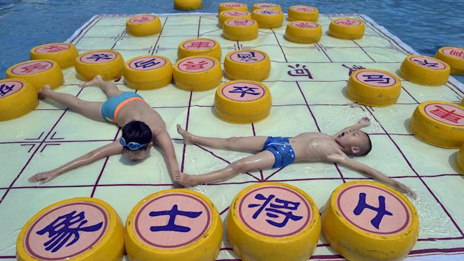 Children cool off on a 20 square meter Chinese chess board, at a water park in Chongqing municipality