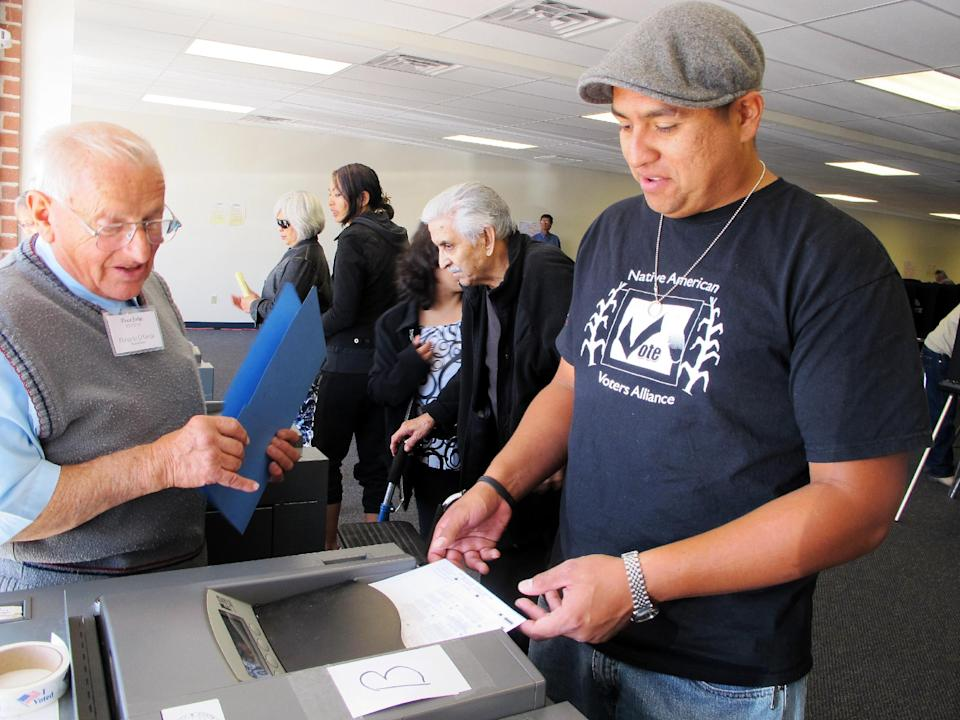 In this Oct. 26, 2012, photo, Dashiell Beardsley, right, feeds his ballot into a voting machine during early voting in Albuquerque, N.M. The National Congress of American Indians and other groups have been working to turn around low voter participation that has persisted in Indian Country for decades. (AP Photo/Susan Montoya Bryan)