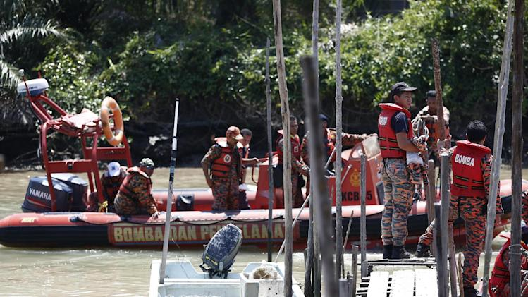 Malaysian Search and rescue personnel return to a port following their search operation for passengers of a sunken boat in outskirt of Banting, Malaysia, Wednesday, June 18, 2014. A wooden boat carrying more than 90 Indonesian migrants capsized and sank after leaving Malaysia's west coast, and rescuers scrambled to save more than 60 people still missing, Malaysia's maritime agency said Wednesday. (AP Photo/Vincent Thian)