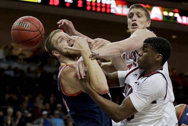 Pepperdine's Brendan Lane, left, vies for a rebound against Saint Mary's Matt Hodgson, center, and James Walker III in the first half of an NCAA college basketball game in the quarterfinals of