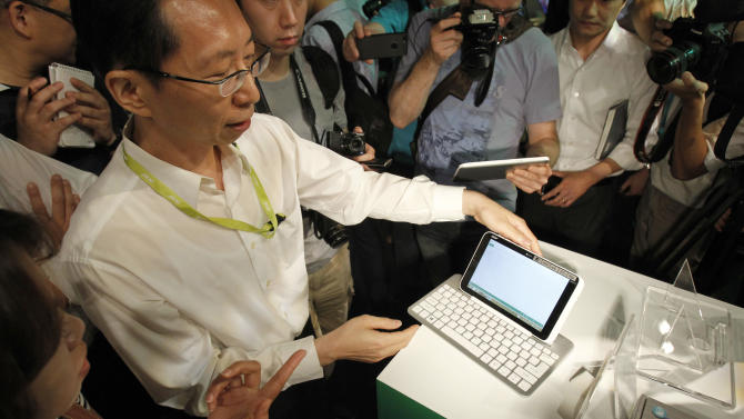 An Acer employee displays a new tablet Iconia W3 at an international press conference on the eve of the opening of Computex , one of the world's largest IT exhibitions, in Taipei, Taiwan, Monday, June 3, 2013. The 8-inch Windows-8 based Iconia W3 tablet combines both home and office functions. (AP Photo/Wally Santana)