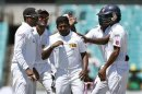 Team mates congratulate Sri Lanka's Rangana Herath after he dismissed Australia's Mitchell Starc during the third day's play of the third cricket test match at the Sydney Cricket Ground