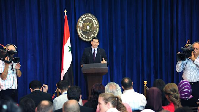 In this photo released by the Syrian official news agency SANA, Syria's foreign ministry spokesman Jihad Makdissi speaks at a news conference in Damascus, Syria, Sunday, July 15, 2012. Syria on Sunday denied U.N. claims that government forces used heavy weapons during a military operation that left scores dead. Makdissi said the violence Thursday was not a massacre as activists and many foreign leaders have asserted but a military operation targeting armed fighters who had taken control of the village of Tremseh. (AP Photo/SANA)