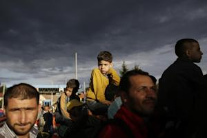 Refugees line up to cross the border from Croatia to…