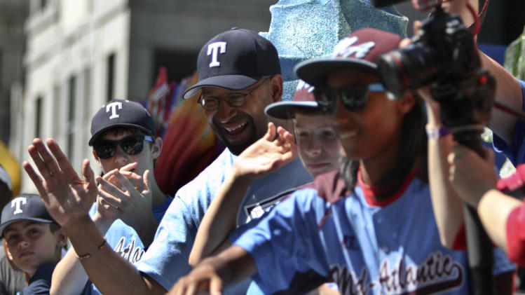 Mayor Michael Nutter, third from left, along with members of the Taney Dragons baseball team are greeted by fans during a parade in Philadelphia, Wednesday Aug. 27, 2014, to celebrate the team's accomplishments during the Little League World Series. (AP Photo/ Joseph Kaczmarek)