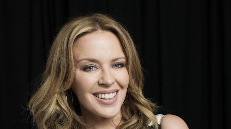 "In this June 19, 2013 photo, Australian recording artist Kylie Minogue poses for a portrait in New York. The singer compiled a book looking back at her fashion choices, particularly her stage costumes, in a new book called ""Kylie Fashion,"" published by Running Press. (Photo by Victoria Will/Invision/AP)"