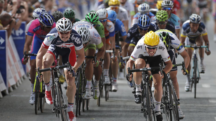 Mark Cavendish of Britain, right with yellow helmet, crosses the finish line ahead of Andre Greipel of Germany, left, to win the second stage of the Tour de France cycling race over 207.5 kilometers (129 miles) with start in Vise and finish in Tournai, Belgium, Monday July 2, 2012. (AP Photo/Laurent Rebours)