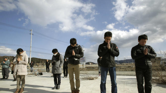People observe a moment of silence in front of what is left of a disaster control center in an area devastated by the March 11, 2011 earthquake and tsunami, in Minamisanriku, Miyagi prefecture, in Japan, Monday, March 11, 2013. Japan marked the second anniversary on Monday of the devastating earthquake and tsunami that left nearly 19,000 people dead or missing.(AP Photo/Shizuo Kambayashi)