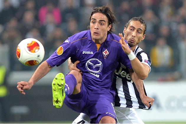 Fiorentina' forward Alessandro Matri, left, and  Juventus defender Martin Caceres, of Uruguay, vie for the ball during an Europa League, Round of 16, soccer match between Juventus and Fiorentina a