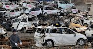 A man strolls next to the wreckage of vehicles in Kesennuma, Miyagi prefecture. Cash earmarked for tsunami reconstruction work has been diverted to unrelated projects, a Japanese government audit has shown, as residents of the devastated northeast vent frustration over the slow pace of rebuilding