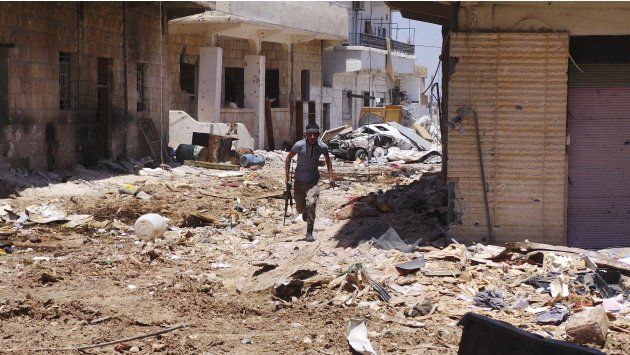 A Free Syrian Army fighter carrying his weapon walks along a street piled with rubble near damaged buildings in Deraa