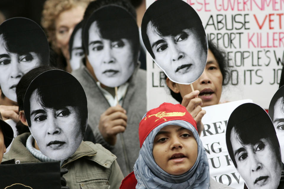 FILE - In this Wednesday, Oct. 24, 2007 file photo, demonstrators wearing masks of Myanmar opposition leader Aung San Suu Kyi demonstrate outside the Chinese Embassy in London to mark her 12th anniversary of house detention by the Myanmar ruling military regime. (AP Photo/Sang Tan)