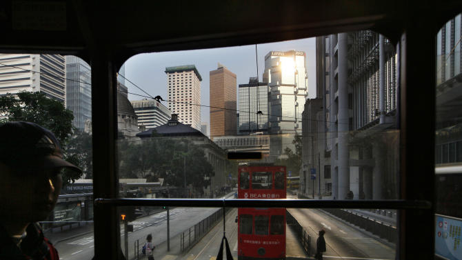 In this Jan. 11, 2013 photo, a man sits on the upper deck of a tram in Central, downtown of Hong Kong. Hop aboard the century-old tram system for an old-fashioned ride through the neighborhoods along the length of the northern edge of the island. (AP Photo/Kin Cheung)