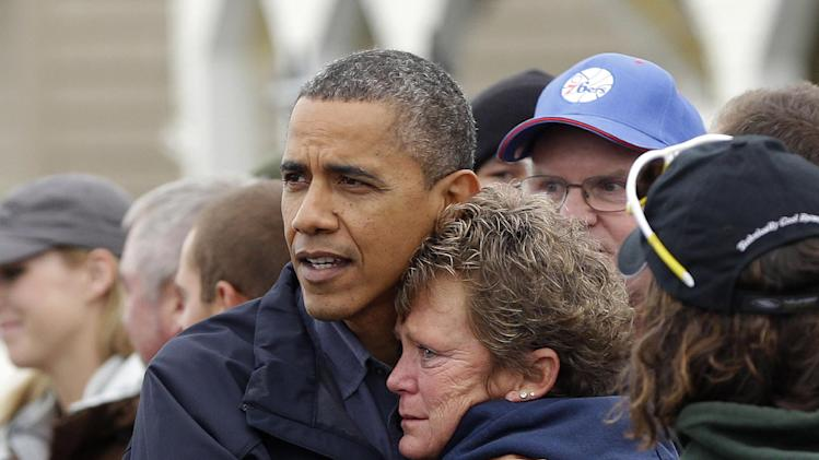 President Barack Obama, left, embraces Donna Vanzant, right, during a tour of a neighborhood effected by superstorm Sandy, Wednesday, Oct. 31, 2012 in Brigantine, N.J.  Vanzant is a owner of North Point Marina, which was damaged by the storm. (AP Photo/Pablo Martinez Monsivais)
