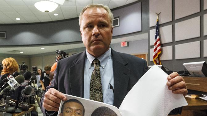 Auburn Police Chief Tommy Dawson holds up head shots of suspect Desmonte Leonard, 22, of Montgomery, Ala., during a news conference, Sunday, June 10, 2012, in Auburn, Ala. Police say Leonard has been charged with capital murder and has not yet been captured, in connection with a shooting at an apartment complex near Auburn University that left three dead and three others injured. Dawson urged Leonard to turn himself in and also said authorities were searching for two other persons of interest. (AP Photo/Opelika-Auburn News, Vasha Hunt)