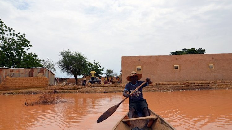 A man rows through floods waters on September 5, 2013 in Niamey, Niger