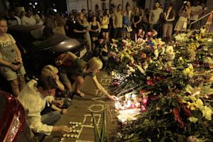 People hold candles and place flower tribute outside…