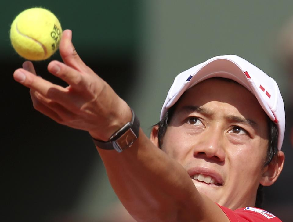 Japan's Kei Nishikori serves to Spain's Rafael Nadal during their fourth round match of the French Open tennis tournament at the Roland Garros stadium Monday, June 3, 2013 in Paris. (AP Photo/Michel Euler)