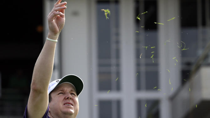 J.J. Henry tosses grass into the air as he prepares to tee off on the first hole at the Tournament of Champions golf tournament on Friday, Jan. 4, 2013 in Kapalua, Hawaii. (AP Photo/Elaine Thompson)