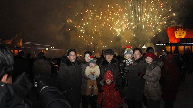 """A North Korean family has their photo taken in front of fireworks as they celebrate the new year on Tuesday Jan. 1, 2013. North Koreans celebrated the arrival of the new year, marked as """"Juche 102"""" on North Korean calendars. """"Juche"""" means """"self reliance,"""" the North Korean ideology of independence promoted by North Korean founder Kim Il Sung, and modern-day North Korean calendars start with the year of his birth in 1912. (AP Photo/Kim Kwang Hyon)"""