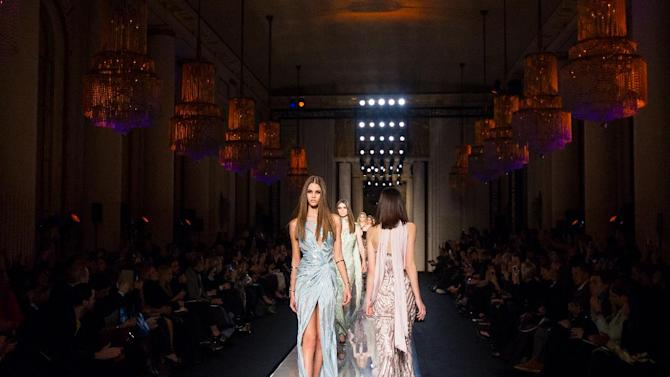 FILE - In this Sunday, Jan. 19, 2014 file photo, models present creations by Italian fashion designer Donatella Versace as part of the Atelier Versace Spring-Summer 2014 Haute Couture fashion collection, presented in Paris. Just a few years ago it was on the brink of extinction, now haute couture - the 150-year-old Parisian tradition of making bespoke, hand-constructed and astronomically-priced gowns - is back. And critics are saying it's more relevant than ever. The fall-winter 2014/15 collection calendar, starting Sunday with Atelier Versace, has this season expanded to five days from three to make room for 12 major houses, as well as collections a whole swathe of up-and-coming names. Additions in recent seasons include the return of big-hitters Donatella Versace, Giorgio Armani and Maison Schiaparelli to the calendar. (AP Photo/Jacques Brinon, file)