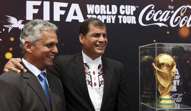 Ecuador's President Correa posses with national soccer team coach Rueda next to the World Cup trophy, in Quito