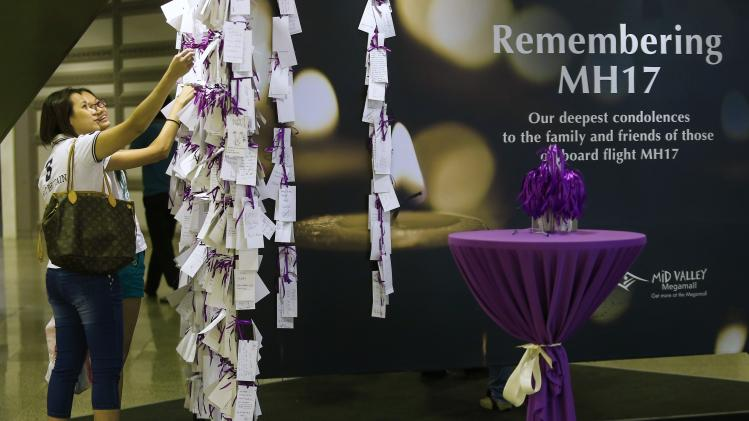 Women look at messages on a dedication board for the victims of downed Malaysia Airlines Flight MH17 in Kuala Lumpur