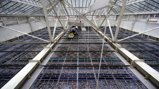A worker cleans stained glass above the Kirchner Cultural Center's main hall in Buenos Aires