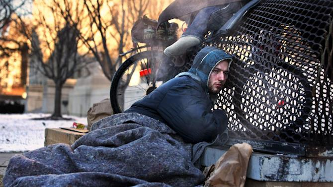 Nicholas Simmons, 20, of Greece, N.Y., warms himself on a steam grate with three homeless men by the Federal Trade Commission, just blocks from the Capitol, during frigid temperatures in Washington, Saturday, Jan. 4, 2014. On New Year's Day, Simmons disappeared from his parents' house in a small upstate New York town, leaving behind his wallet, cellphone and everything else. Four days later, an Associated Press photographer, looking for a way to illustrate unusually cold weather, took his picture as he warmed himself on a steam grate a few blocks from the U.S. Capitol. His parents Paul and Michelle Simmons saw the photograph in USA Today Sunday morning after it was brought to their attention through a Facebook page set up to help find their son, according to police and family friends, and were able to report his location to D.C. police who transported him to a hospital where he was reunited with his father and brother who drove all day to find him. (AP Photo/Jacquelyn Martin))