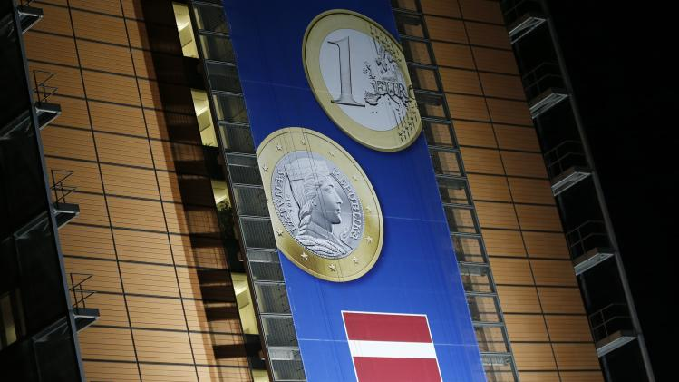 A banner showing a Latvian Euro coin is seen on the facade of the EU Commission headquarters in Brussels