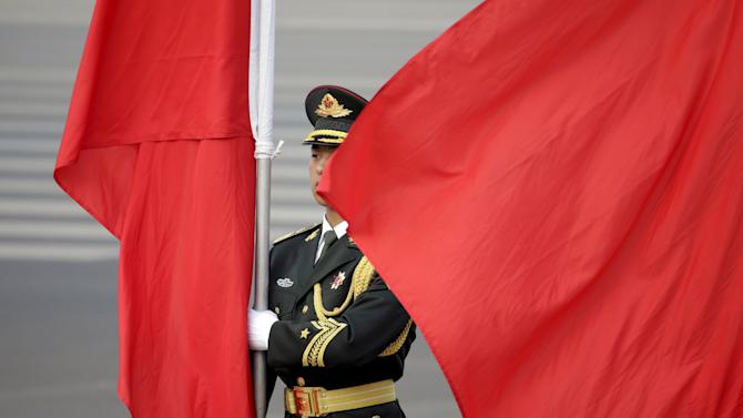 A soldier from an honour guard holds red flag during a welcoming ceremony in Beijing