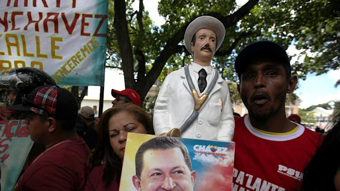 Supporters of Venezuela's President Hugo Chavez hold up a picture of him alongside a statue of Venezuelan folk-saint Doctor Jose Gregorio Hernandez outside the National Assembly  in Caracas, Venezuela, Saturday, Jan. 5, 2013. Venezuelan lawmakers are meeting to select a new president of the National Assembly in a session that could give clues to the future of the country amid uncertainty about ailing Chavez.  The late Doctor Jose Gregorio Hernandez gained fame in Venezuela for giving free treatment and medicine to the poor. (AP Photo/Fernando Llano)
