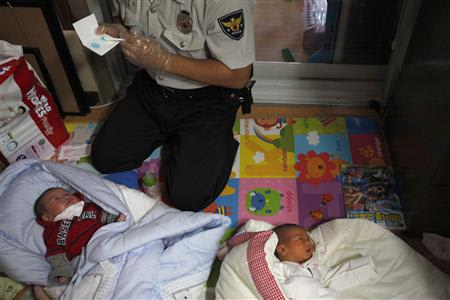 "A police officer collects DNA samples from two abandoned babies after the babies were left at a ""baby box"" at Joosarang church in Seoul September 20, 2012. A South Korean pastor of the church who runs a ""baby box"" where mothers can leave unwanted infants has seen a sharp increase in the number of newborns being left there because, the pastor says, of a new law aimed protecting the rights of children. South Korea is trying to shed a reputation of being a source of babies for adoption by people abroad. It is encouraging domestic adoption and tightening up the process of a child's transfer from birth mother to adoptive parents. Picture taken September 20, 2012. REUTERS/Kim Hong-Ji"