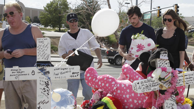 """Actor Christian Bale and his wife Sibi Blazic, at right, carry flowers to place on a memorial to the victims of Friday's mass shooting, Tuesday, July 24, 2012, in Aurora, Colo. Twelve people were killed when a gunman opened fire during a late-night showing of the movie """"The Dark Knight Rises,"""" which stars Bale as Batman. (AP Photo/Ted S. Warren)"""
