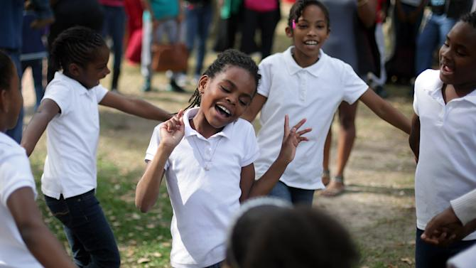 "Kalylah Carter, 8, sings Beyonce's ""Love on Top"" as other G.E.M.S. with God's Servant Ministries dance in a circle during Martin Luther King, Jr. Day celebrations at McKenzie Park on Monday, Jan. 21, 2013, in Panama City, Fla. (AP Photos/News Herald, Heather Leiphart)"