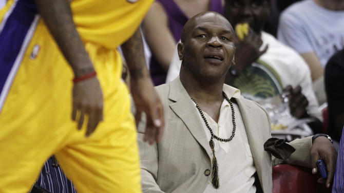 FILE - In this Oct. 13, 2010, file photo, Mike Tyson watches an NBA preseason basketball game between the Los Angeles Lakers and the Sacramento Kings in Las Vegas. Tyson will be heading to China in December to help promote boxing there.  (AP Photo/Julie Jacobson, File)