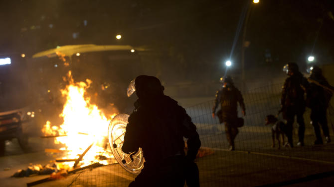 Riot police walk in front of a burning barricade made by protestors in Rio de Janeiro's sister city, Niteroi, Brazil, Wednesday evening, June 19, 2013. Rio de Janeiro and Sao Paulo city leaders said Wednesday that they reversed an increase in bus and subway fares that ignited anti-government protests. Many people doubted the move would quiet the demonstrations which have moved well beyond outrage over the fare hikes into communal cries against poor public services in Latin America's biggest nation. (AP Photo/Silvia Izquierdo)