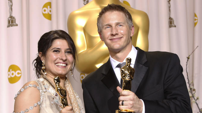 """Sharmeen Obaid-Chinoy, left, and Daniel Junge pose with their awards for best documentary short for """"Saving Face"""" during the 84th Academy Awards on Sunday, Feb. 26, 2012, in the Hollywood section of Los Angeles. (AP Photo/Joel Ryan)"""