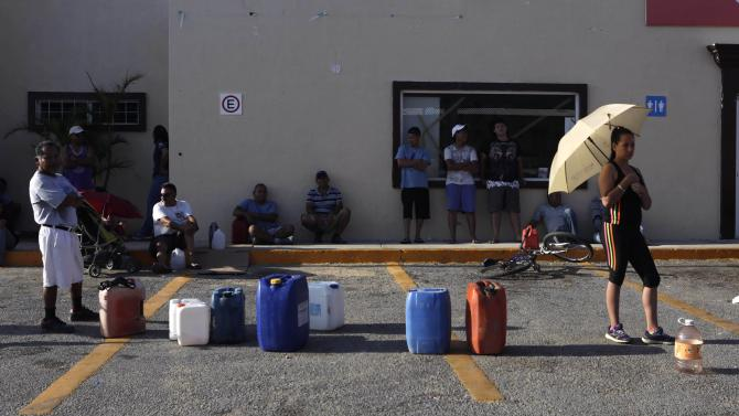 People wait in line to buy gas at a  Pemex gas station in San Jose del Cabo, after Hurricane Odile hit in Baja California
