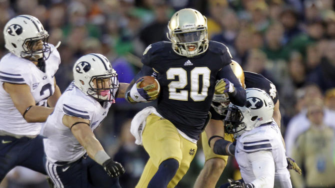 FILE - In this Oct. 20, 2012, file photo, Notre Dame running back Cierre Wood, center, cuts between Brigham Young defenders Spencer Hadley, left, Daniel Sorensen, left center, and Joe Sampson during the second half of an NCAA college football game in South Bend, Ind. Notre Dame defeated BYU 17-14.  With the national championship on the line, two throwback offenses will slug it out. No. 1 Notre Dame and No. 2 Alabama rely heavily on the run, and that doesn't figure to change in the biggest game of the year. (AP Photo/Michael Conroy, File)