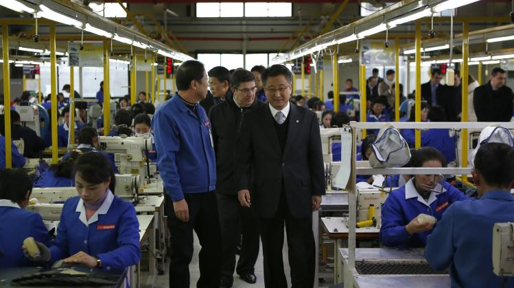 Hong, chairman of the Kaesong Industrial District Management Committee, takes a tour in a factory of a South Korean company with officials from the G20 Seoul Conference at the Joint Industrial Park in Kaesong
