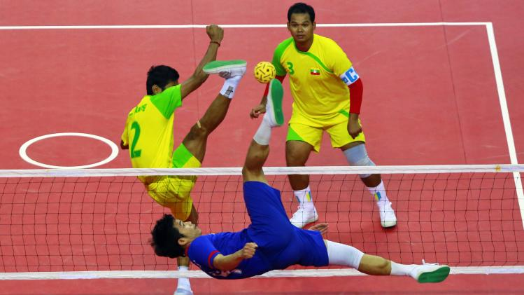 Laos' Chakkaphanh K fights for the ball with Myanmar's Zaw Zaw Aung as Sithu Lin looks on during their men's Team Double final sepak takraw match at the 27th SEA Games in Naypyitaw
