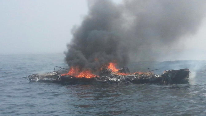 In this photo provided by the U.S. Coast Guard, a 25-foot pleasure craft is engulfed in flames 3 miles north of Neah Bay, Wash., Sunday, Aug. 3, 2014. The man had been on the raft for nearly an hour Sunday when an agency helicopter hoisted him up and transported him to a hospital. Petty Officer 3rd Class Katelyn Shearer says she didn't know his condition, but he was able to walk into the facility. It's not yet known what caused the fire on the vessel that split in half and sank. (AP Photo/U.S. Coast Guard)